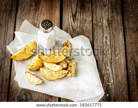 Potato wedges and salt shaker on rustic vintage planked wood table - snack bar or pub menu. Background layout with free text space. - stock photo
