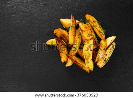 Potato wedges on black background. Top view. - stock photo