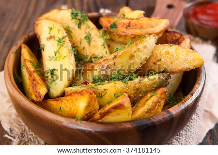 Potato wedges with dill in wooden bowl on wooden background - stock photo
