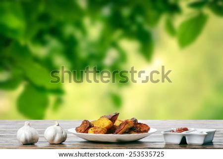 Potato wedges with garlic and tomato sauce  - stock photo