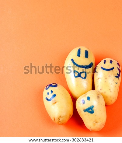 Potato with funny face on the table - stock photo