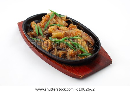Potato with mushrooms on a hot frying pan on a white background