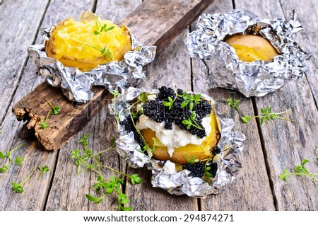 Potatoes baked in foil completely with cream cheese and black caviar - stock photo