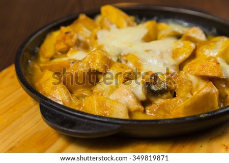 Potatoes baked with cheese in a frying pan. - stock photo