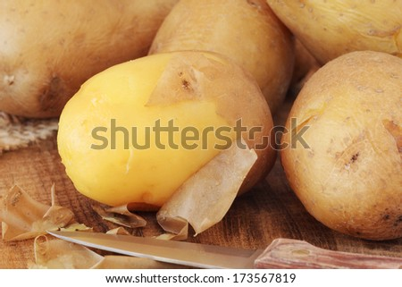 Potatoes boiled in their skins in the process of peeling them off - stock photo