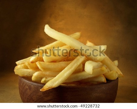 Potatoes fried in oil in the foreground on colored background - stock photo