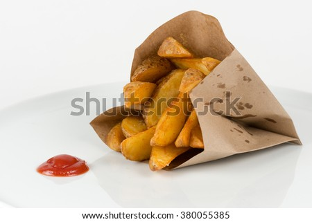 Potatoes fries in a paper bag with ketchup isolated on white - stock photo