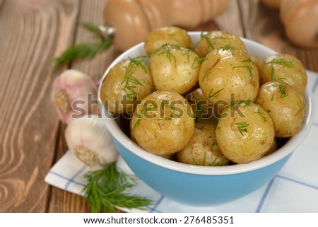 Potatoes in a blue bowl on a brown background - stock photo