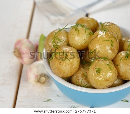 Potatoes in a blue bowl on a white background - stock photo