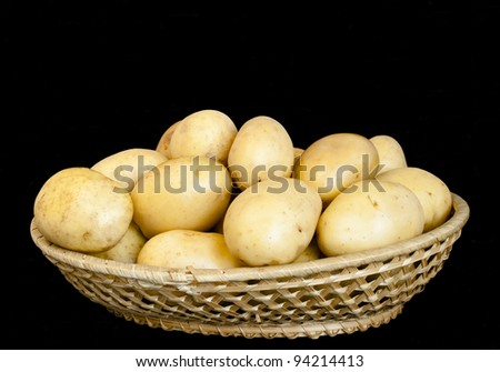 Potatoes in wicker bowl isolated on black background - stock photo