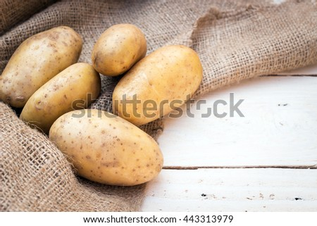 Potatoes on old sack with wooden background. Copy space for text.  - stock photo