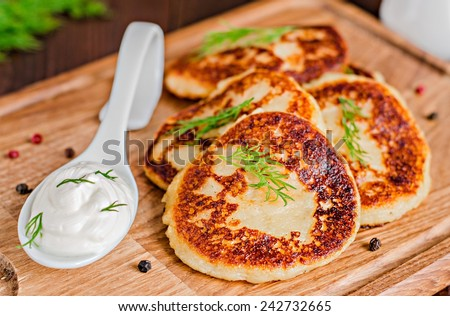 Potatoes pancakes with fennel on wooden plate. Toned image. Selective focus - stock photo