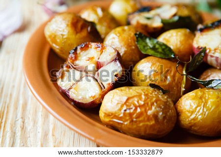 Potatoes roasted in their jackets with garlic, food close up - stock photo