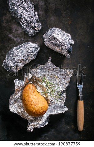 Potatoes roasted in their skin in aluminium foil on a summer BBQ being unwrapped for a tasty accompaniment to a meal or appetizer - stock photo