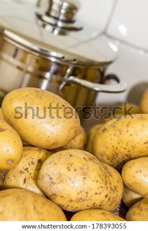 potatoes with coocking pot close up, angled view - stock photo