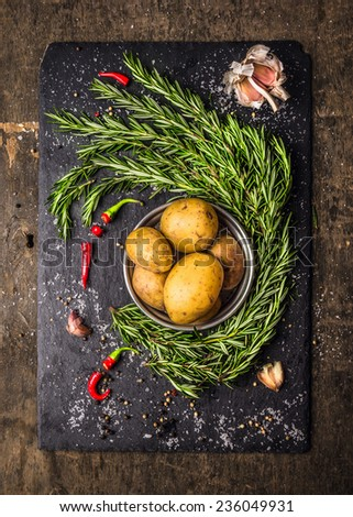 Potatoes with rosemary, garlic and spices, raw ingredients on slate and dark wooden background - stock photo