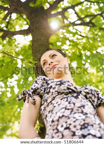 potrait of attractive caucasian woman leaning on tree at sunset and looking away. Low angle view, vertical shape - stock photo