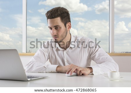 Potrait of attractive focused businessman using laptop computer at his office desk