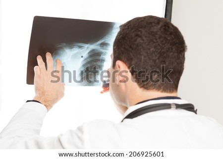 potrait of doctor looking at chest x ray - stock photo