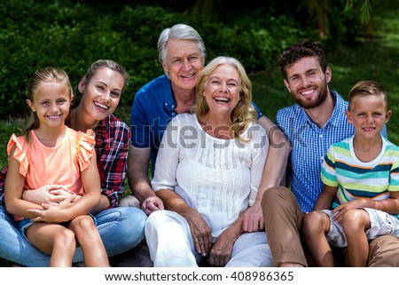 Potrait of hapy family relaxing on grass at yard - stock photo