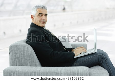 Potrait of mature businessman sitting on couch in office lobby, using laptop computer.
