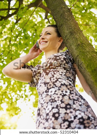 potrait of mid adult italian woman leaning on tree at sunset and talking on mobile phone. Low angle view, vertical shape. - stock photo