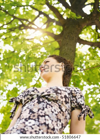 potrait of sad woman leaning on tree at sunset and looking away. Low angle view, vertical shape - stock photo
