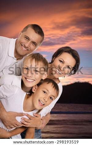 Potrait of the cheerful family embracing in the sunset together - stock photo