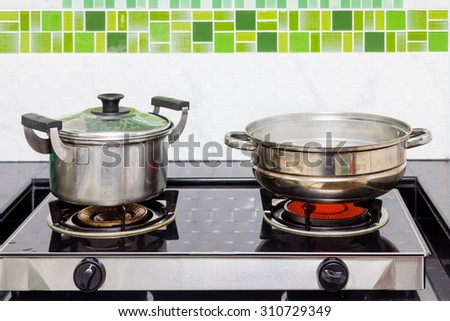 Pots and steaming pot on the stove - stock photo