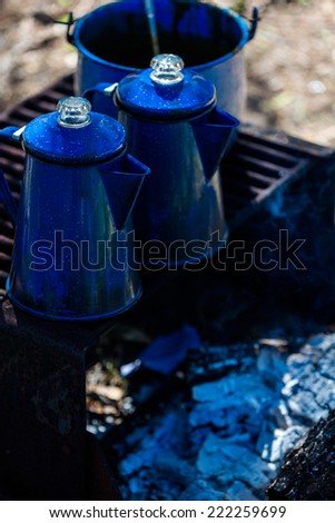 Pots boiling water on camping fire pit with wood. - stock photo
