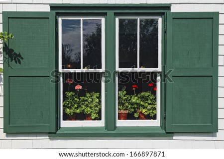 Pots of flowering geraniums in the window of Green Gables House, made famous by the Anne of Green Gables books by L. M. Montgomery.  Located in Cavendish, Prince Edward Island, Canada. - stock photo