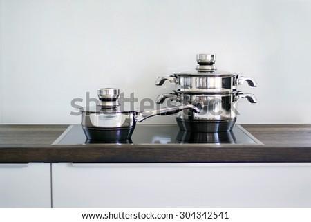 Pots on black hob in modern kitchen - stock photo