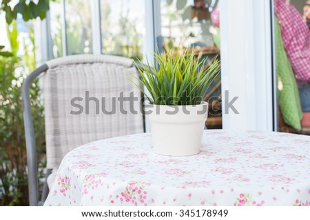 Potted grass on table outdoors.