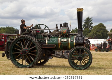 POTTEN END, UK - JULY 27: A large vintage traction engine leaves the parade grounds heading toward the vehicle preparation area at the Dacorum Steam fair on July 27, 2014 in Potten End - stock photo