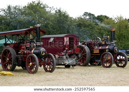 POTTEN END, UK - JULY 27: A pair of vintage traction engines stand outside the main arena waiting to be ushered into the grand parade at the Dacorum Steam & Country fair on July 27, 2014 in Potten End - stock photo