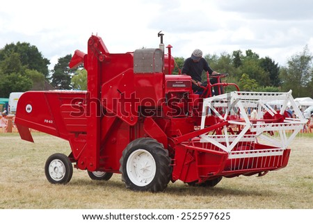 POTTEN END, UK - JULY 27: A vintage McCormick International combine harvester gives a working display to the watching public at the Dacorum Steam & Country fair on July 27, 2014 in Potten End - stock photo