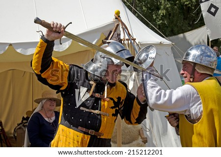 POTTEN END, UK - JULY 27: Two medieval man at arms reenactors play out a possible scene from a medieval combat using period weapons and armour at the Dacorum Steam fair on July 27, 2014 in Potten End