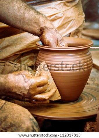 Making clay pot on the pottery wheel artisan hands and pottery tools