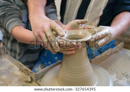 potter teaches the student the art of clay pottery - stock photo