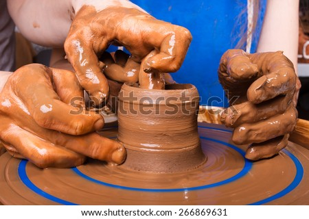 Potter teaches to sculpt in clay pot - stock photo