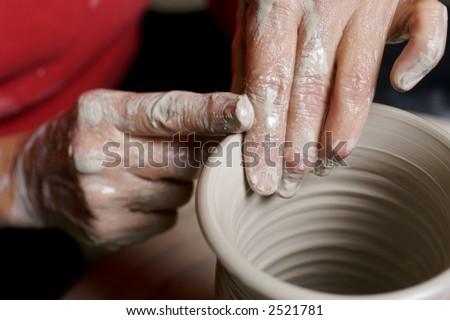 Potter working clay on potter's wheel - stock photo