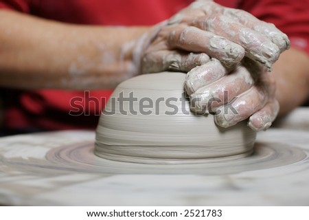 Potter working clay on potter's wheel