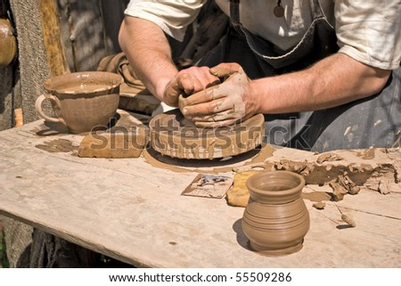 Potter working with clay on potter's wheel