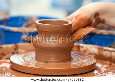 Pottery craft wheel ceramic clay potter human hand - stock photo