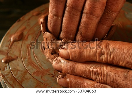 pottery craftsmanship red clay potter hands work finger closeup - stock photo