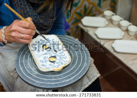 Pottery decorator from Caltagirone while finishing a ceramic dish in her work space - stock photo
