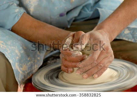 Pottery making close-up. Craftsman's hands shape clay into a  fictility on a spinning wheel.