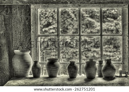 Pottery on a Shelf in Front of a Window Covered in Cobwebs - stock photo