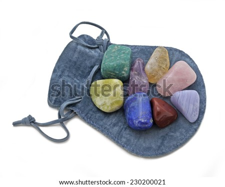 Pouch with Chakra Crystal Set  -  Chakra Crystal Set of  eight rainbow colored stones placed on a blue cloth pouch on a white background - stock photo