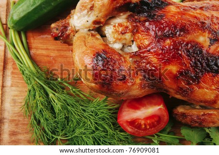 poultry : fresh grilled whole chicken with black olives and raw tomatoes on wooden board isolated over white background - stock photo